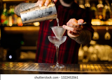 Bartender pouring a Courpse Reviver cocktail from the steel shaker on the bar counter on the blurred background