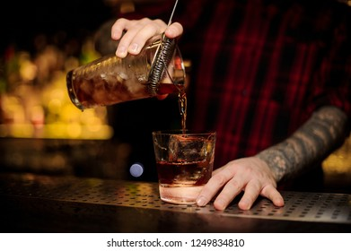 Bartender pouring a delicious Godfather cocktail from the measuring cup through the strainer to a glass with big ice cube on the bar counter