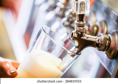 Bartender pouring draft beer in the bar.