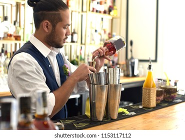Bartender bartender is pouring a drink into the jigger