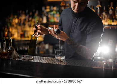 Bartender pouring drink making a cocktail from the steel jigger to the glass on the bar counter