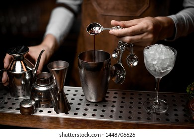 Bartender pouring an essence from the spoon to the steel shaker on the bar counter in the dark blurred background