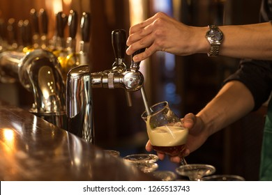Bartender pouring and filling glasses with fresh delicious beer. Worker of brewery serving alcohol at bar counter. Concept of beer house, lager and pub.