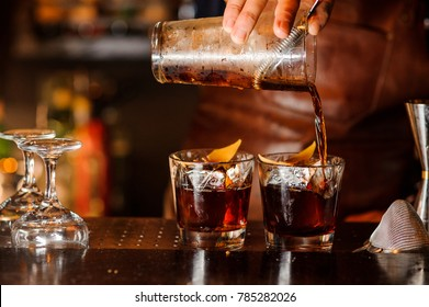 Bartender pouring fresh alcoholic drink into the glasses with ice cubes on the bar counter