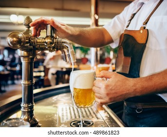 Bartender pouring the fresh beer in one of Czech traditional pubs - Shutterstock ID 489861823