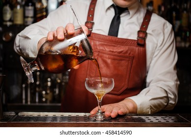 Bartender pouring fresh cocktail in fancy glass