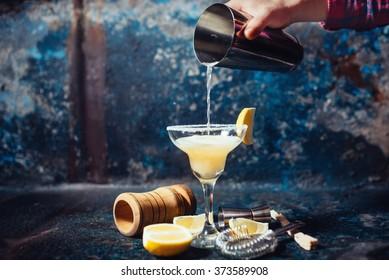 Bartender pouring fresh lime margarita in fancy glass at restaurant