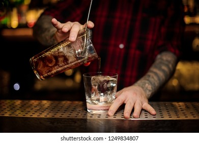 Bartender pouring a Godfather cocktail from the measuring cup through the strainer to a glass with big ice cube on the bar counter