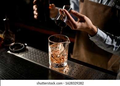 Bartender pouring a golden brown alcoholic drink from the steel jigger to a glass on the bar counter