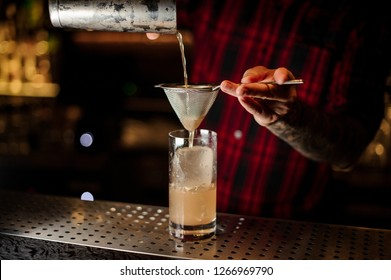 Bartender pouring a Lemonade cocktail from the steel shaker through the strainer on the bar counter on the blurred background
