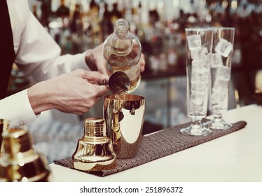 Bartender is pouring liquor in golden shaker, toned image