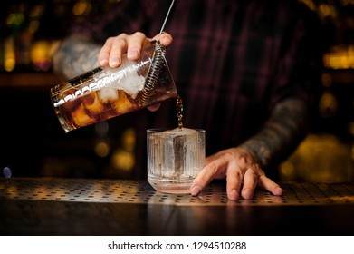 Bartender pouring a Old Fashioned cocktail from the measuring cup to a glass on the bar counter