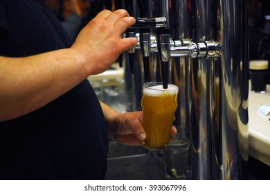 Bartender pouring a pint of draft beer from the crane