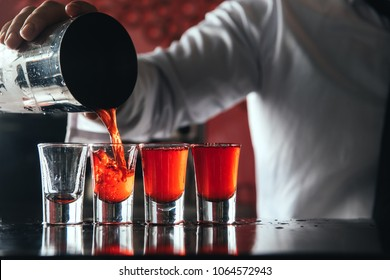 Bartender pouring strong alcoholic drink into small glasses on bar. Red shots at the nightclub. Red alcoholic drink in glasses on bar. Red cocktail at the nightclub. Barman preparing cocktail shooter