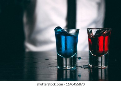Bartender pouring strong alcoholic drink into small glasses on bar. Blue and red shots at nightclub. Colorful cocktails at the nightclub. Barman preparing cocktail shooter.