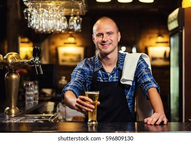 Bartender pouring from tap fresh beer into the glass in pub