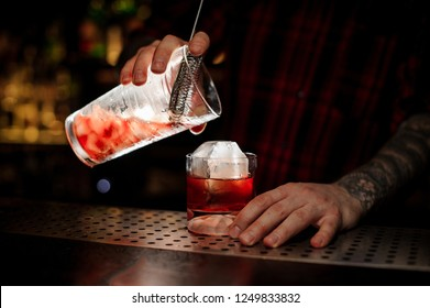 Bartender pouring a tasty Boulevardier cocktail from the measuring cup through the strainer to a glass with big ice cube on the bar counter