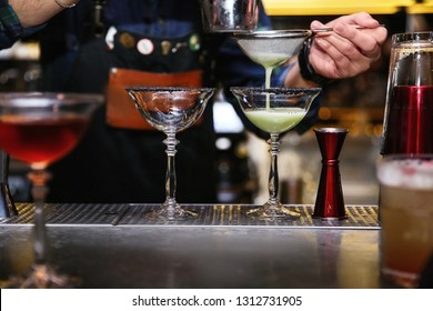 Bartender pouring tasty cocktail at counter in nightclub, closeup