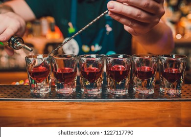 Bartender is pouring tequila into glass against the background of the bar.