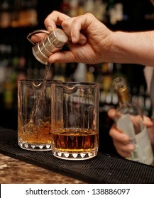 Bartender is pouring whisky in glass on the bar counter