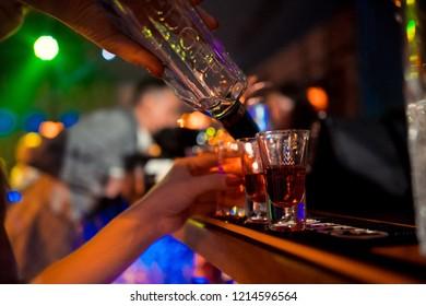 Bartender pours alcoholic cocktails.