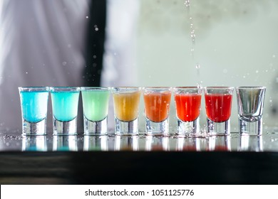Bartender pours alcoholic drink into small glasses on bar. Colorful cocktails at the bar. Colorful shots at the club. Alcoholic drink in different colors. Nightlife scene. Shots at the bar table.