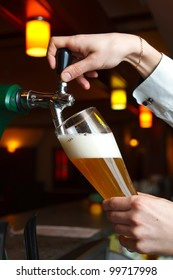 bartender pours beer into glass from tap