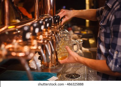 The bartender pours a beer at Oktoberfest closeup