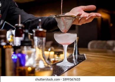 the bartender pours a cocktail into a glass