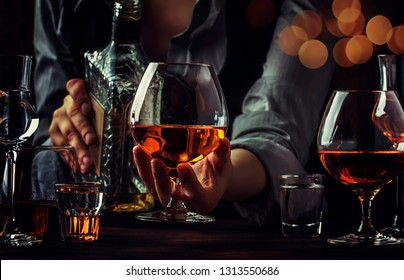 The bartender pours the cognac or brandy in big wine glass on the old bar counter. Vintage wooden background in pub or bar, night mood. Place for text, toning, selective focus