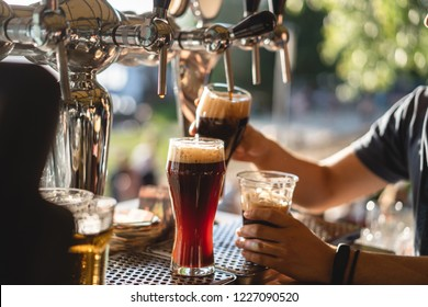 bartender pours dark beer in a glass at the bar close-up