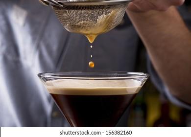 bartender pours espresso martini cocktail