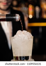 bartender pours the liquor in a cocktail