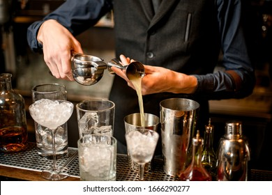 bartender pours squeezed juice from a beaker into a shaker. Near the man staying glasses with ice and bottles of alcohol.