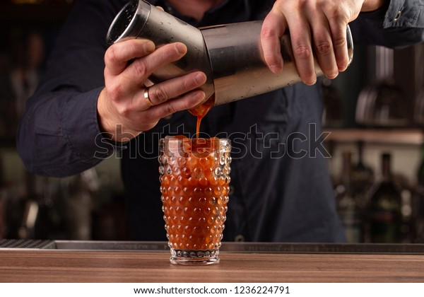 bartender pours tomato red juice from the shaker, making a cocktail, drink