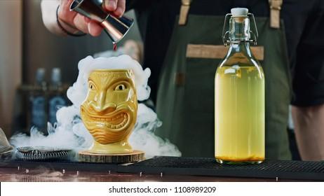 bartender prepares tiki cocktail