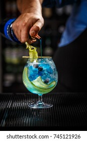 Bartender preparing a blue gin tonic with curacao