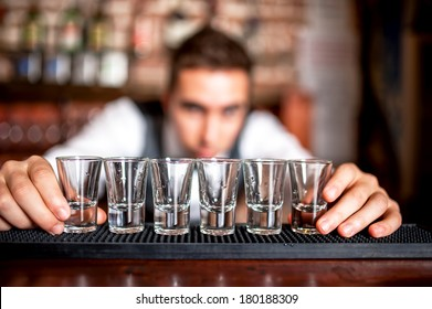 bartender preparing and lining shot glasses for alcoholic drinks on bar