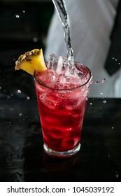 Bartender preparing red cocktail at the bar. Splashing red cocktail. Red cocktail at the club.