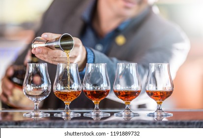 Bartender professional preparing five alcololic drinks. He pouring a very high quality rum or cognac.