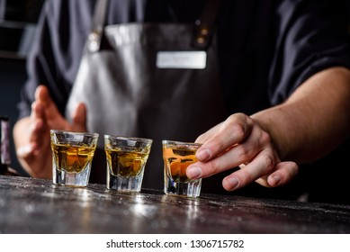 The bartender puts three glasses of whiskey on a dark wooden bar in a nightclub. Close-up. Lined horizon