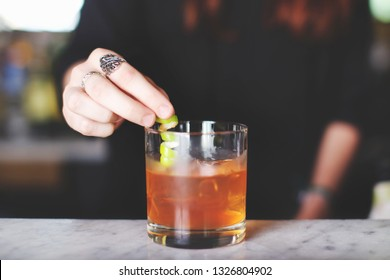 Bartender putting lemon twist in a cocktail at a bar
