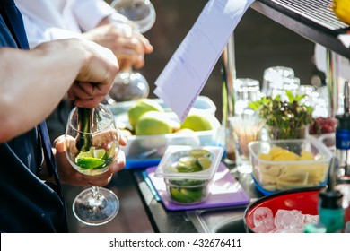 Bartender putting lime into glass. Muddling lime to make a cocktail. Barman holding glass