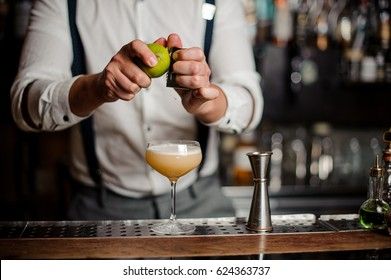 bartender is rubbing a lime and making a cocktail noface