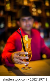 Bartender serving an alcohol cocktail glass in a bar