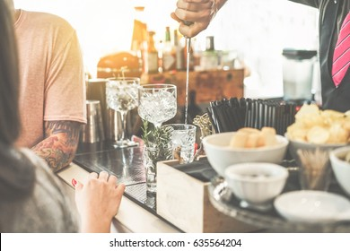 Bartender serving cocktail in american bar outdoor - Young tattoo people waiting for drink at sunset - Soft focus on hand metal pour - Lifestyle,nightlife and entertainment concept - Vintage filter