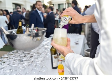 Bartender serving a cold drink pouring the liquor in the glass to offer it to the customer of the restaurant.