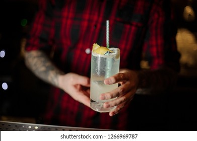 Bartender serving a delicious Gin Fizz cocktail in the glass with tubule and orange zest on the bar counter