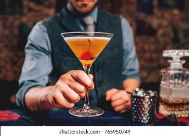 Bartender serving manhattan cocktail in martini glass