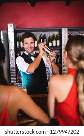 Bartender shaking cocktail in cocktail shaker at bar counter in nightclub
